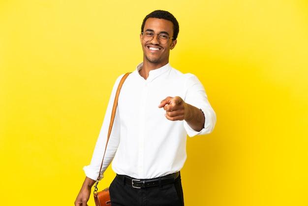 행복 한 표정으로 앞을 가리키는 고립 된 노란색 배경 위에 아프리카 계 미국인 사업가