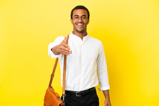 Афро-американский деловой человек на изолированном желтом фоне, пожимая руку для заключения хорошей сделки