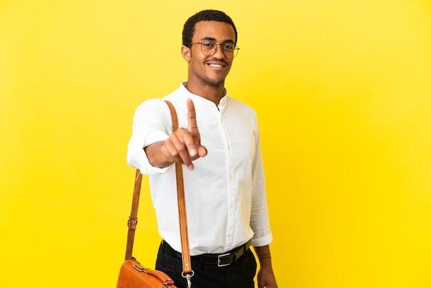 손가락을 보여주고 들어올리는 고립된 노란색 배경 위에 아프리카계 미국인 사업가