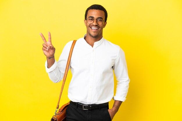 Афро-американский деловой человек на изолированном желтом фоне улыбается и показывает знак победы