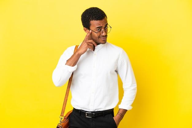 アイデアを考えて孤立した黄色の背景にアフリカ系アメリカ人のビジネスマン