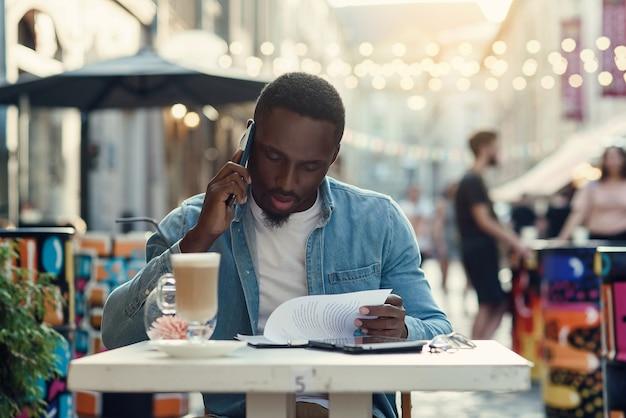 アフリカ系アメリカ人のビジネスマンは、紙の文書を読み、電球のある屋外カフェに座っているラップトップで作業します。