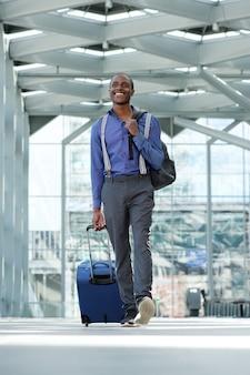 手荷物と空港で歩いているアフリカ系アメリカ人のビジネスマン