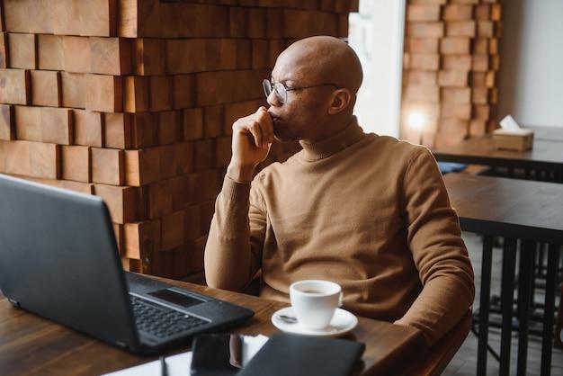 Афро-американский деловой человек с ноутбуком в кафе