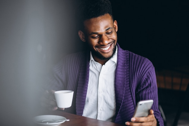 African american business man with phone and coffee in a cafe