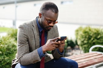 African American business man works in his smartphone sitting on the bench outside