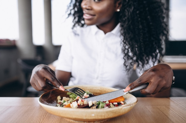 African american business woman eating salad in a cafe close up