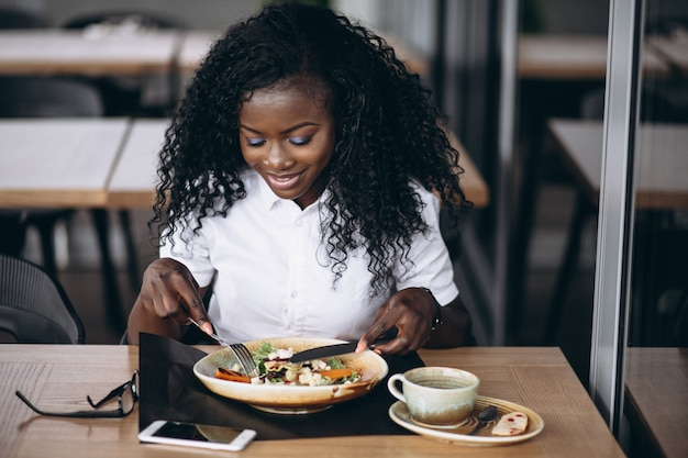 African american business woman eating salad in a cafe