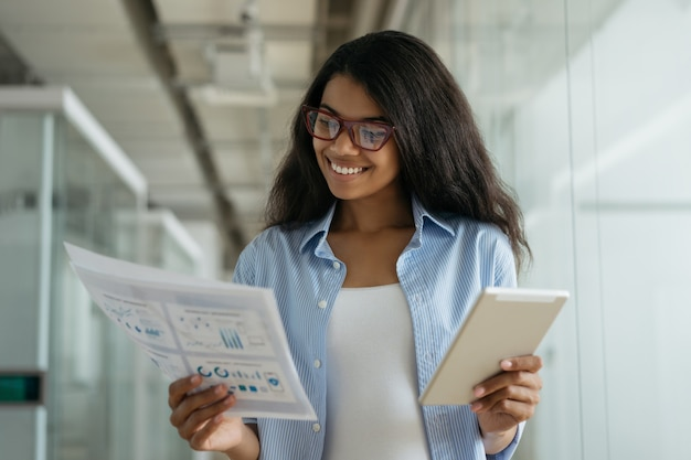 デジタルタブレットと紙の文書を保持し、情報を読んで、オフィスで働くアフリカ系アメリカ人のビジネスウーマン
