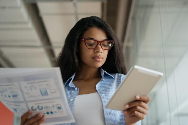 現代のオフィスでデジタルタブレットを使用して、紙の文書を保持しているアフリカ系アメリカ人のビジネスウーマン