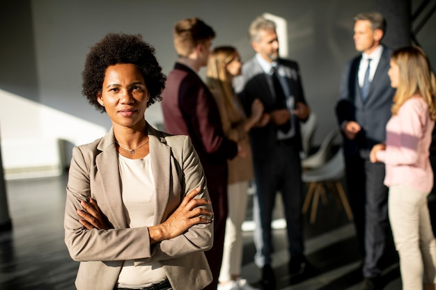African american business woman standing in front of her team in the office