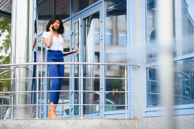 Афро-американская деловая женщина разговаривает по мобильному телефону в офисном здании