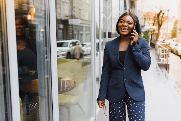 Афро-американская деловая женщина разговаривает по мобильному телефону возле офисного здания