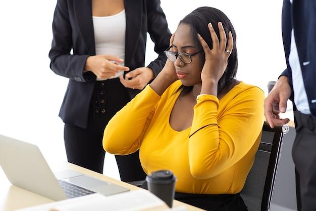 아프리카계 미국인 사업가는 심각한 실수와 나쁜 일을 화나게 했습니다. 남자와 여자 동료 왕따와 그녀에 손가락을 가리키는 여성 동료를 비난