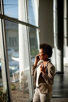 화창한 날에 사무실에서 창으로 휴대 전화를 사용하는 아프리카 계 미국인 비즈니스 우먼