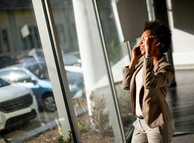 African american business woman using mobile phone by the window in the office on sunny day