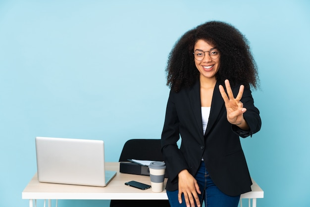 African american business woman working in her workplace happy and counting three with fingers