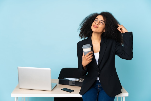 African american business woman working in her workplace having doubts and thinking