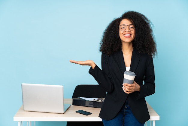 African american business woman working in her workplace holding copyspace imaginary on the palm to insert an ad