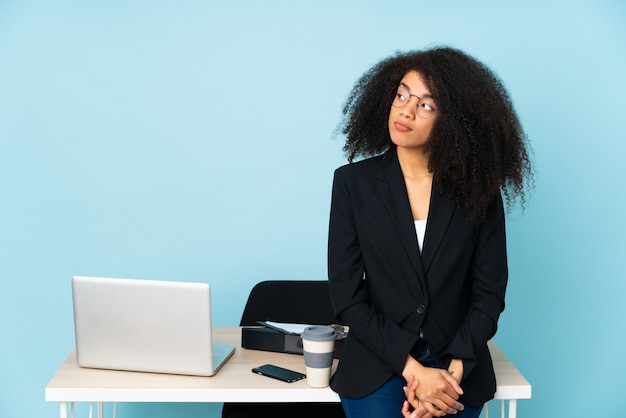 African american business woman working in her workplace making doubts gesture looking side