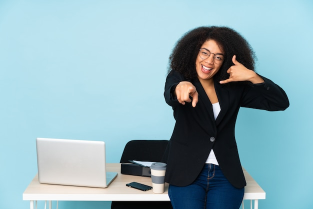 African american business woman working in her workplace making phone gesture and pointing front