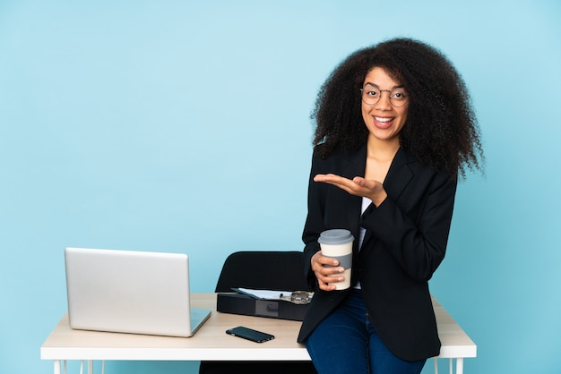 African american business woman working in her workplace presenting an idea while looking smiling towards