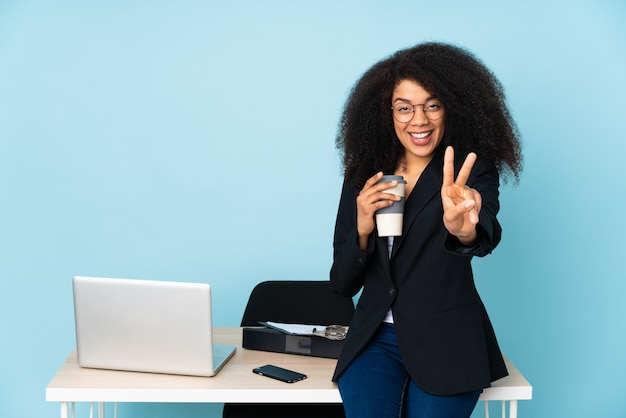 African american business woman working in her workplace smiling and showing victory sign