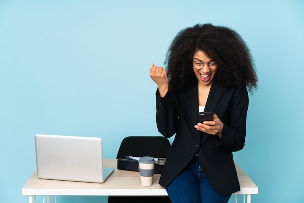 African american business woman working in her workplace surprised and sending a message