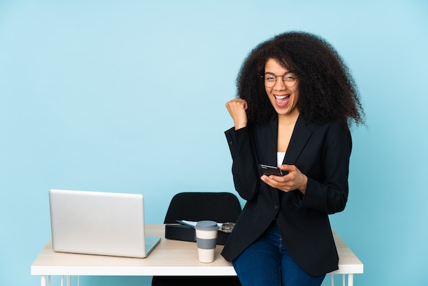 African american business woman working in her workplace with phone in victory position