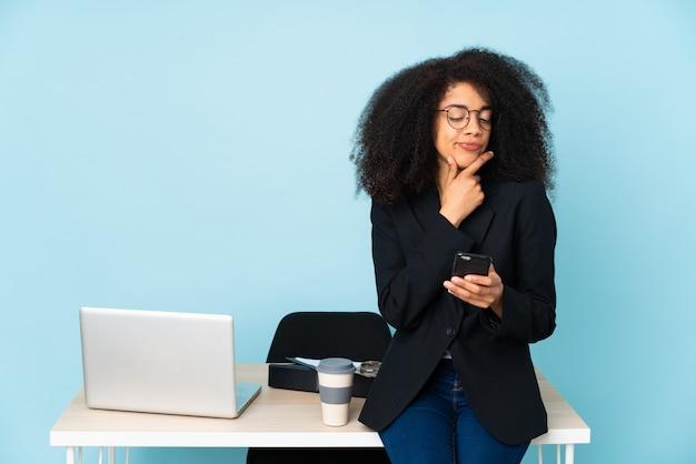 アフリカ系アメリカ人ビジネスの女性が彼女の職場で働くと考え、メッセージを送信