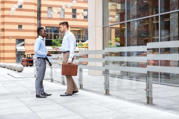 아프리카 계 미국인 사업가 및 백인 사업가 논의하고 도시에 문서를보고