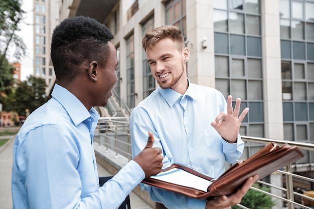 Афро-американский бизнесмен и кавказский бизнесмен улыбается и разговаривает
