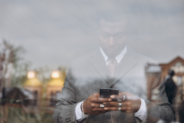 African american businessman in classic grey suit holding a smartphone.