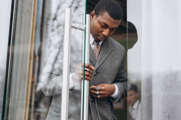 African american businessman in classic grey suit while leaving the office building