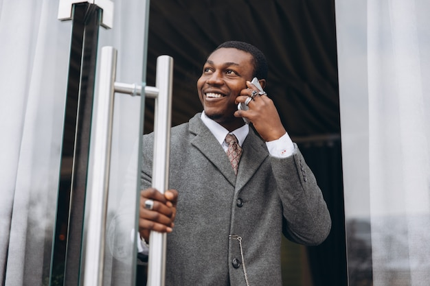 African american businessman in classic grey suit while leaving the office building.