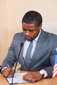 African-american businessman or delegate in suit sitting by table in front of microphone and looking through text of his report