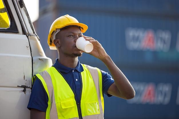 커피를 마시는 아프리카 계 미국인 사업가, 흑인 남자는 야외 컨테이너 작업장에서 커피 브레이크를