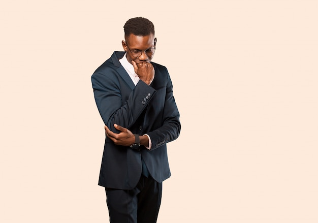 African american businessman feeling serious, thoughtful and concerned, staring sideways with hand pressed against chin against beige wall