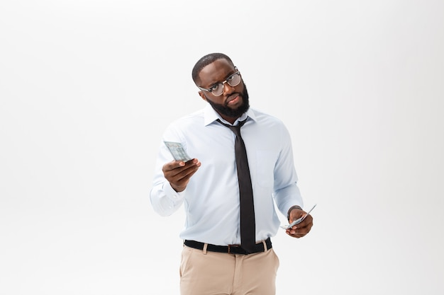African american businessman holding cash and serious looking at camera. indoor, isolated on gray background.