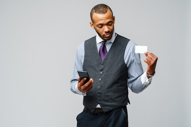 African-american businessman holding credit card and mobile cellular phone.