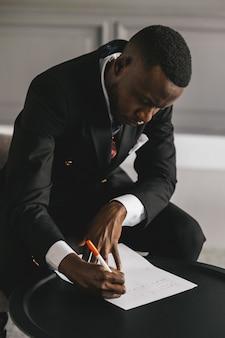 Афро-американский бизнесмен в костюме делает заметки на листе бумаги, сидя в своем офисе у камина