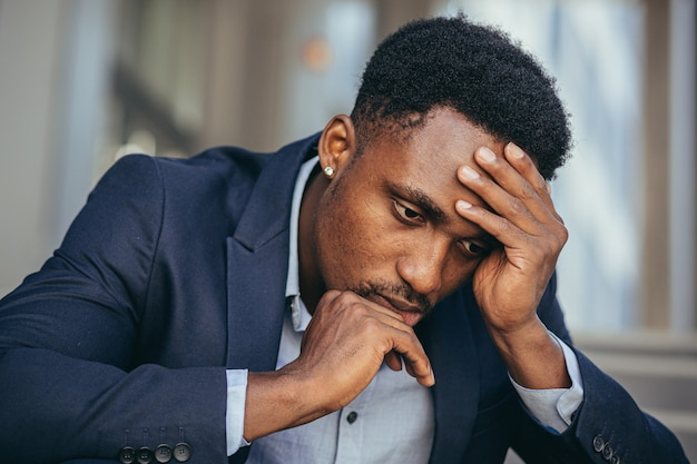 비즈니스 정장을 입은 아프리카계 미국인 사업가는 직장에서 나쁜 소식을 듣고, 계단에 앉아 우울하게 해고되고, 클로즈업 초상화 사진