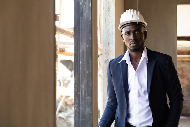 건설 현장에 청사진 계획을보고 보호 안전 하드 모자에 아프리카 계 미국인 사업가.