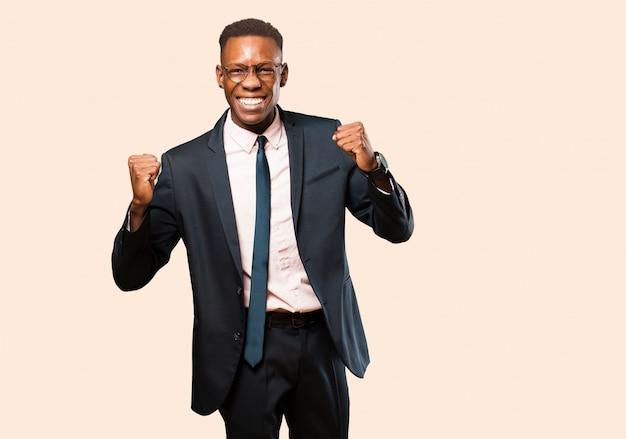非常に幸せと驚きを探しているアフリカ系アメリカ人のビジネスマン、成功を祝って、叫び、ベージュの壁にジャンプ