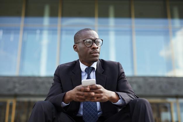 屋外でリラックスしたアフリカ系アメリカ人のビジネスマン
