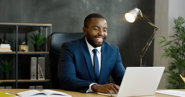 African american businessman sitting at table and having videochat on laptop computer.