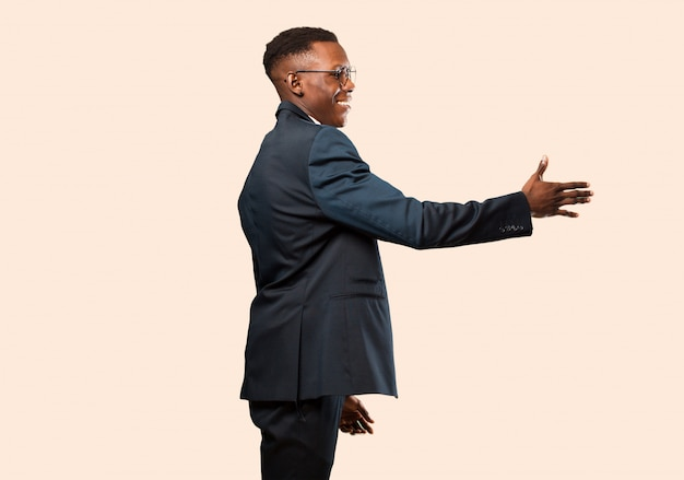 African american businessman smiling, greeting you and offering a hand shake to close a successful deal, cooperation concept against beige wall