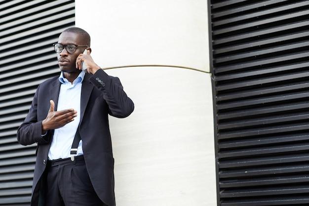 Афро-американский бизнесмен разговаривает по телефону в городе