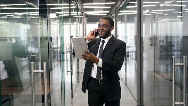 African american businessman talking on smartphone while walking in corporate office building and checking email messages online at tablet pc. successful businessman concept.