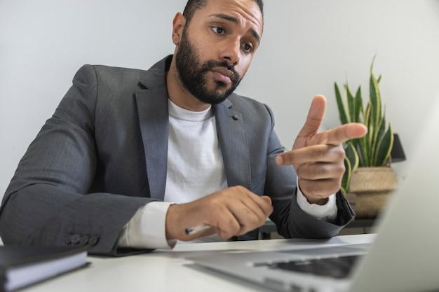 Афро-американский бизнесмен разговаривает с коллегой по видеозвонку, указывая пальцем на экран ноутбука